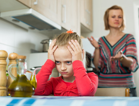 berate: Frustrated mother scolding little daughter at home Stock Photo