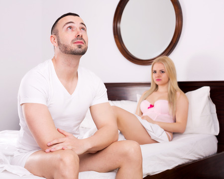 unsatisfied: Sad young girlfriend and depressed man arguing in bedroom