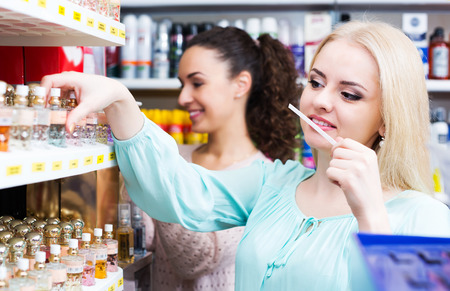 eau de toilette: Cheerful woman friends buying perfume in fragrance section of supermarket