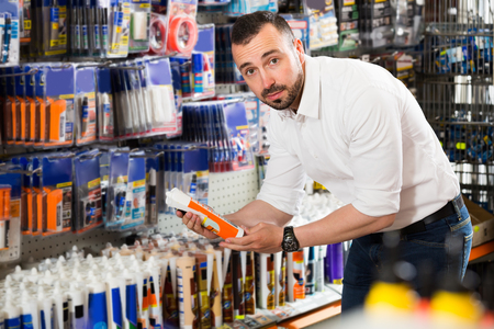 selecting: Portrait of male customer selecting sealant bottle in household department Stock Photo