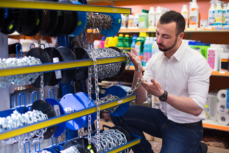 selecting: Portrait of ordinary male customer selecting metallic chain in household department