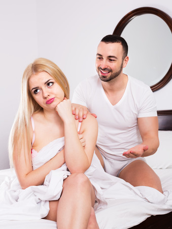 remit: Upset young man comforting offended woman in bedroom Stock Photo