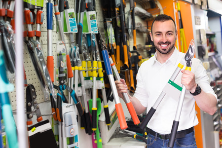 secateur: Portrait of smiling man selecting household tools in household department Stock Photo