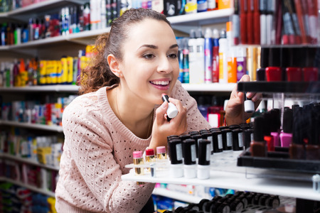beauty shop: Portrait of smiling young brunette selecting lipstick at beauty shop