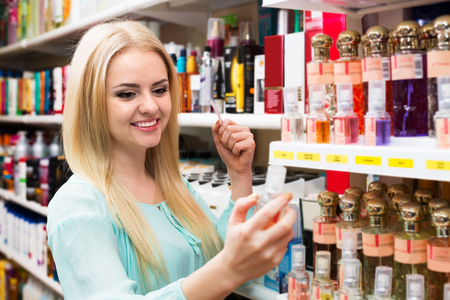 eau de perfume: Portrait of smiling young blondie shopping in beauty store