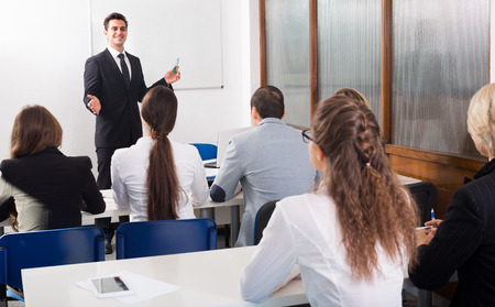 attentive: Attentive students with teacher in classroom at business training