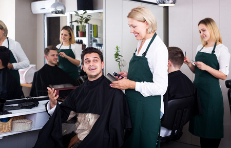 19's: Happy senior female doing hairstyle for adult man in hairdressing saloon Stock Photo
