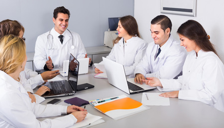specialists: Group of smiling specialists in white overalls having discussion of research work