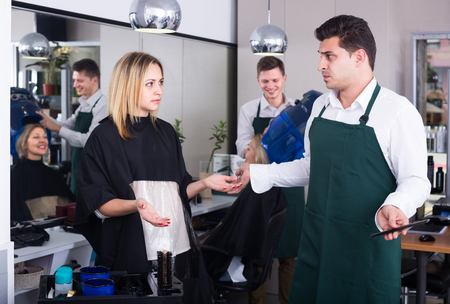 peignoir: Blond young girl complaining on new haircut in hair salon