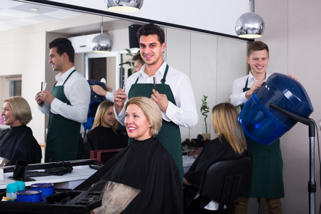 hairdressing saloon: Positive dark-haired man doing hairstyle for smiling mature blonde in hairdressing saloon