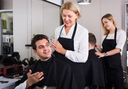 19's: Elderly female hairdresser cutting hair of Indian guy in barbershop and smiling. Focus on guy