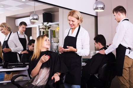 16s: Elderly woman cuts hair of blonde girl at the hair salon Stock Photo
