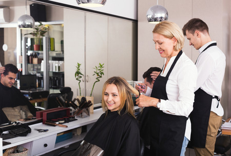 19's: Positive aged woman cutting girl hair in the barbershop Stock Photo