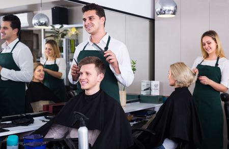 peignoir: Male hairdresser cutting hair of teenage guy in barbershop