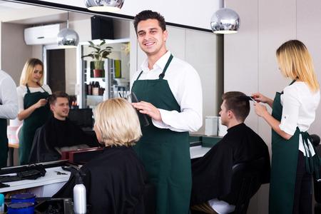 hair stylist: Positive professional stylist cutting hair of elderly blonde in salon