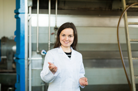 bottling: Portrait of woman near oil bottling machine in manufacturing environment Stock Photo