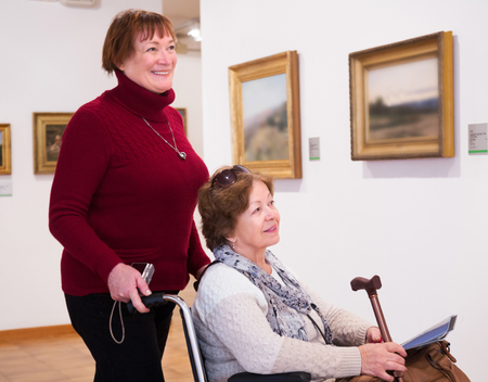 75s: Mature woman and positive senior disabled friend in art gallery Stock Photo