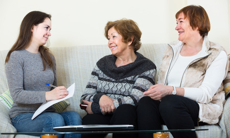 spanish home: positive spanish  account manager helping elderly women with finances at home