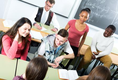 Sorridente giovani studenti di diverse nazionalità seduta e parlando in classe durante la pausa Archivio Fotografico - 59146763