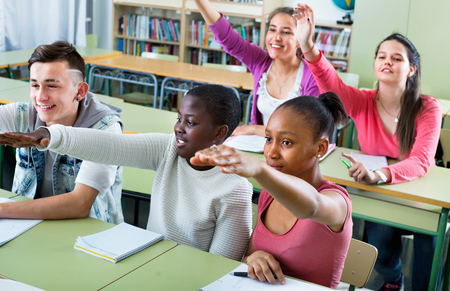 multiple ethnicities: Group of happy school pupils want to give the answer and raise their hands up