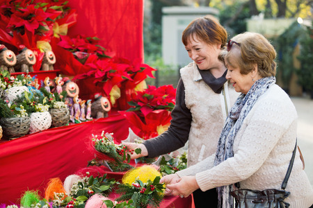 75s: Happy mature women selecting floral compositions at Christmas market