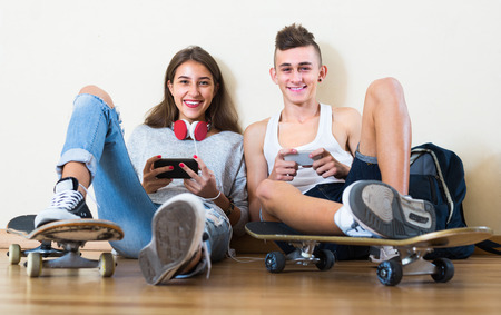 16s: Two joyful smiling teenagers sitting on floor and relaxing with mobile phones Stock Photo