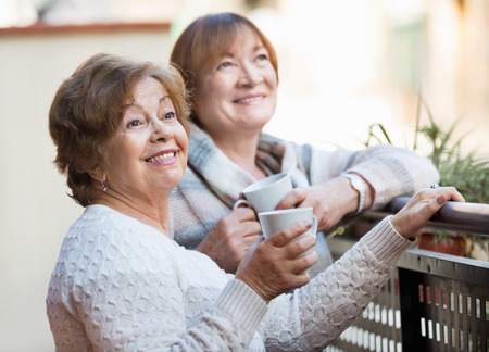 vestidos antiguos: Portrait of positive happy female pensioners drinking tea and smiling on balcony