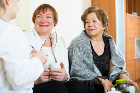 health problems: Two senior women discussing health problems with female therapeutist
