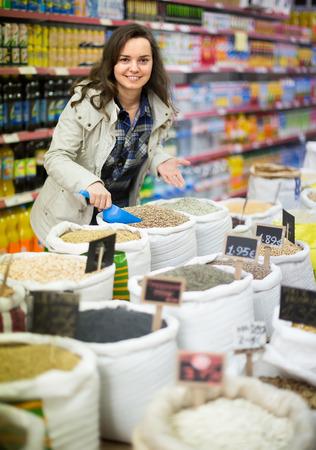 Alegre sorridente jovem morena comprando grumos no supermercado