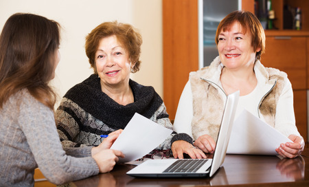 75s: Portrait of happy mature women with papers and agency employee
