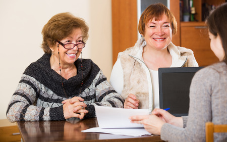Female agent consulting cheerful elderly women in office Stock Photo