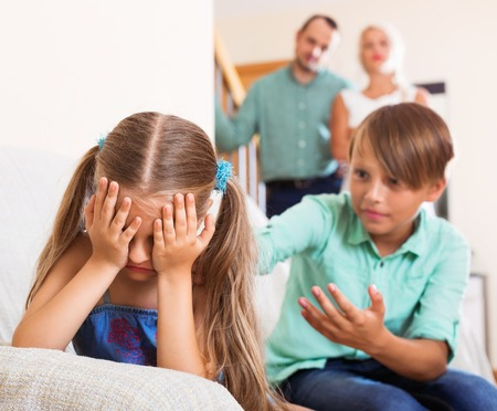 brother sister fight: Brother sister calms crying in the presence of parents at home Stock Photo