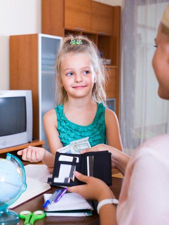 money pocket: Asignaci�n de dinero de bolsillo: Ni�a sonriente linda con el monedero y la madre en el hogar