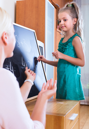 introducing: Positive woman introducing numbers to small girl at home
