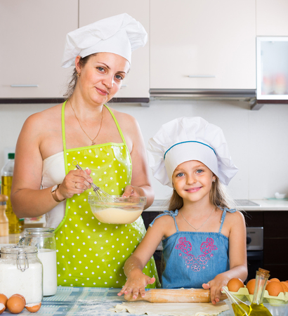 spanish woman: Adult spanish woman and her small assistant kneading paste