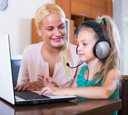 relatives: Happy blonde woman and her little daughter chatting with relatives online