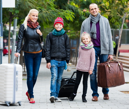 spouses: Family journey: happy spouses with children walking and luggage