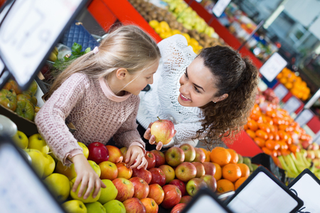 purchasers: Happy mother and little daughter choosing seasonal fruits in grocery