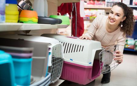 petshop: Portrait of adult girl purchasing pet kennels in petshop Stock Photo