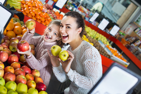 purchasers: Young positive mother and little daughter choosing seasonal fruits in grocery
