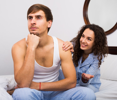 condone: Misunderstood wife trying to reconcile with offended husband in bedroom Stock Photo