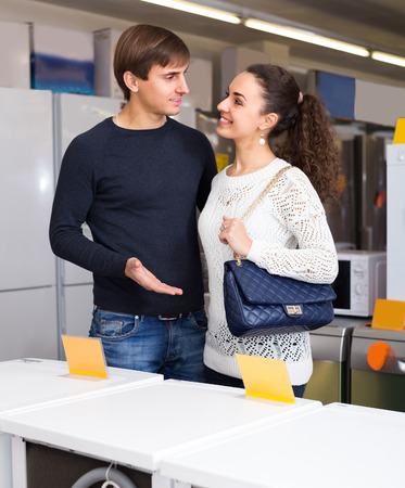 hobs: Portrait of positive young couple at household appliances section of supermarket