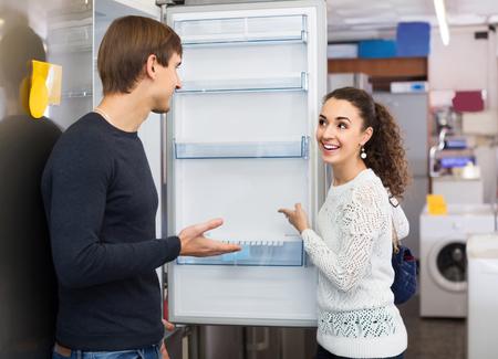 clase media: clase media europea pares de la familia que elige el nuevo refrigerador en hipermercado