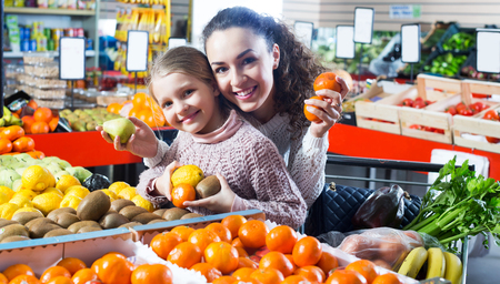 purchasers: Happy adult woman and daughter purchasing fruits and smiling in store