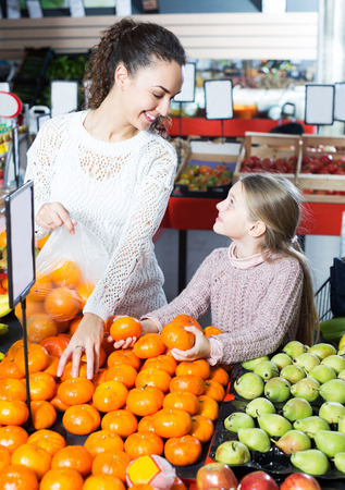 purchasers: Brunette young woman and happy daughter purchasing fruits and smiling in store