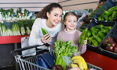 purchasers: Positive female and cheerful smiling little girl shopping green veggies in grocery Stock Photo