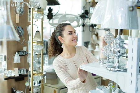 interior lighting: Adult girl buying lighting units for interior in household store