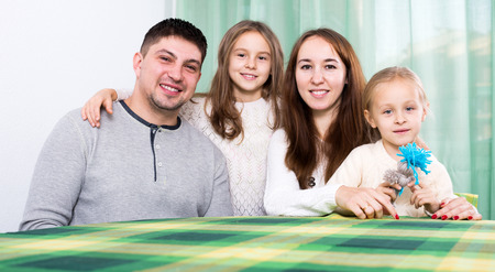 gladful: Ordinary cheerful family of four at table in living room at their home
