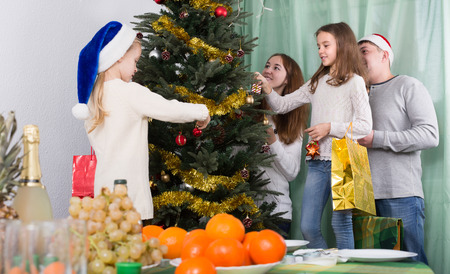 home decorating: Smiling young parents and two little daughters decorating Christmas tree together at home. Selective focus Stock Photo
