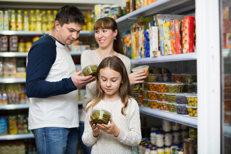 tinned: Happy young parents with little girl buying tinned food at grocery Stock Photo